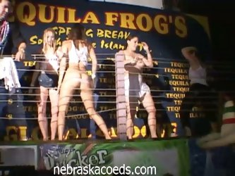 Coeds dance on stage in wet t-shirt contest during spring break