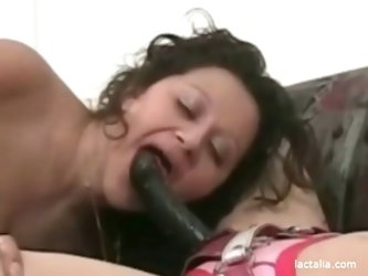 Chubby, busty lesbian rides on a strapon