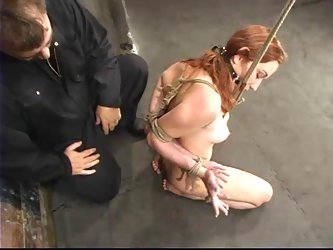 A mechanism pumps Smokie Flame's pussy in BDSM