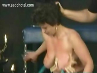 German master puts wooden clamps on large tits covered in candlewax and nipples of big slave and hits her with a whip