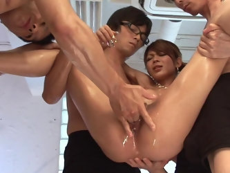 Riana Saotome surrounded by raunchy guys who cover her body with oil. After that, boys grab sex toys and stretch girl's pussy before she sucks al