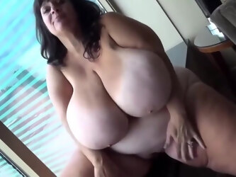 Voluptuous brunette is slowly taking off her clothes and showing us her massive milk jugs