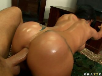 Sporty black haired woman looks very seductive when her body is covered with thick layer of massage oil. Dude sits on the chair and bitch slowly goes