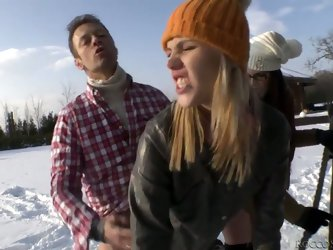 An adorable blonde sucks two lucky guy's wangs out in public -- and in the snow, too. That can't feel good on her knees. But whatever, right