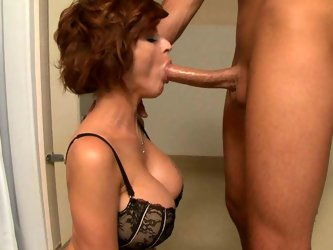 Astonishing redhead MILF with juicy jugs is sucking hard dick deepthroat sitting down on her knees. She then takes off her bra exposing big boobs. She