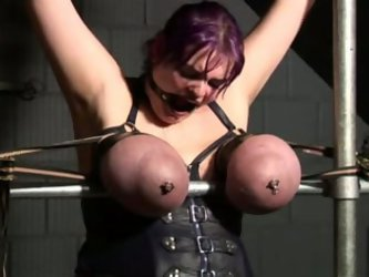 Chunky whore is bounded by her arms and legs to the plank. Kinky master ties up her big boobs and spanks them pretty hard.