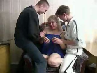 Mature and busty blonde slut from Russia is having fun with two young men. She sucks their fresh dicks and they bang her doggy style!