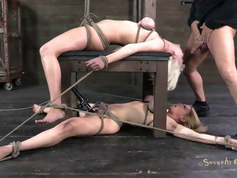 Cherry Torn and Darling are tied to a table in the dungeon. One's on the top and the other is underneath the table. They have their tits tied up