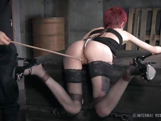 Cadence is kept captive down in the basement. The slutty short-haired redhead is wearing a mouth gag, chains, kinky stockings and high heels. The dirt