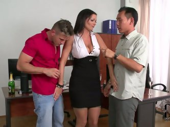 Lustful brunette boss has got curvaceous body shape. She flirts with two guys in the office. They sip champagne to enhance the mood. She reveals her b