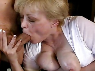 Busty mature with a huge appetite for cock is sucking this guy like a whore, she grabs his penis and balls and gives him a hot head and titjob giving