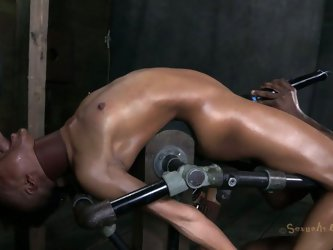 Kinky slim black chick is fixed to the wooden bar. She's bent over it. Her hands and legs are tied with ropes. He oil covered tits are pinned wit