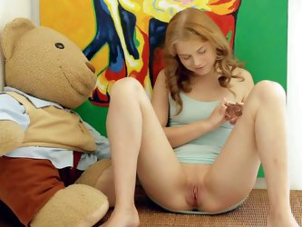Angelic teen cutie Ksenija A plays with her bald pink pussy with legs apart in her room side by side with her favorite plush toy. She sticks glass dil