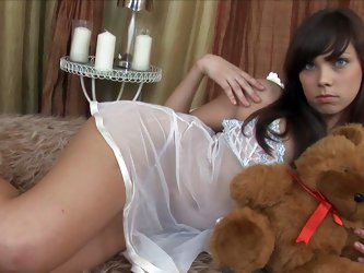 Barely legal brunette Veronika poses in see-through white lingerie with her teddy bear in hands. Her revealing panties leave nothing to imagination!