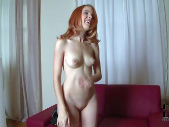 Sexy and aroused playful redhead babe enjoys in taking her clothes off and showing her pale and handsome body and shaved slit on the couch in front of