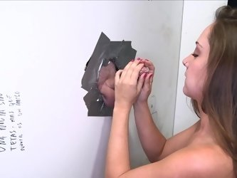 A brunette is getting a big dick inside her mouth in a glory hole