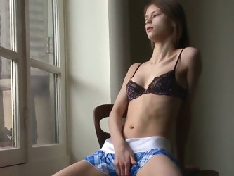 Teen girl Beata plays with her fresh and plump pussy in front of the window
