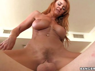 Janet Mason is a horny hot bodied mature redhead. This nasty milf with fake tits gives head and then rides cock like crazy in the middle of the room.