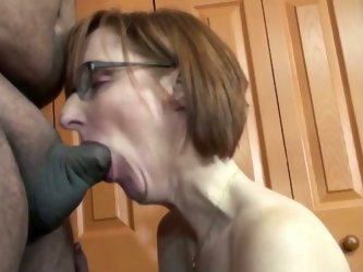 Lustful amateur redhead mom wearing glasses is trying to satisfy a fat guy indoors. She kneels in front of him and begins sucking and rubbing his shor