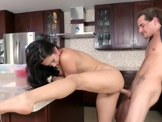 A bimbo with a trimmed pussy is on top of her partner in the kitchen