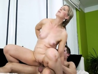 A blonde granny is getting cumshot by a young man on the bed
