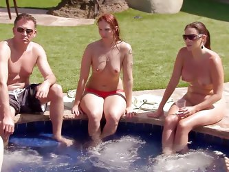 Two young sexy girls climb on the back of their man to have a game of chicken in the water. After the game they head to the hot tub to relax and have