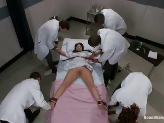 Coed Britney Stevens is tied up to special medical couch and then examined, touched and caressed by doctors Bobby Bends, Dietrich Cyrus, James Deen, J