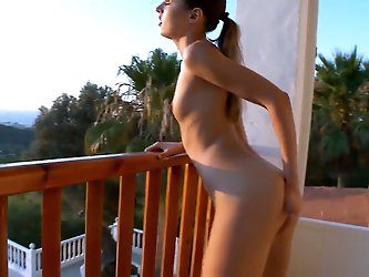 Young and skinny chick Ivana meets the first ray of the sun with her naked sensitive boobs and wet pussy. She goes to the balcony and spreads her legs