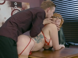 Two people are spending some really productive time in the office by fucking each other's brains out. The redhead secretary with huge tits and gl